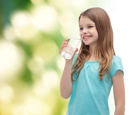green water: health and beauty concept - smiling little girl with glass of water