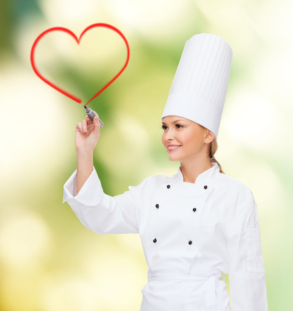cooking, new technology , advertisement and food concept - smiling female chef with marker drawing red heart on virtual screen photo