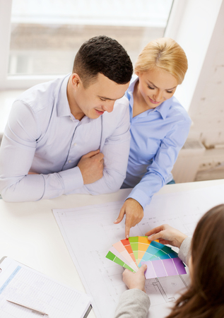home, design and architecture concept - smiling couple looking at blueprint and color samples at office photo