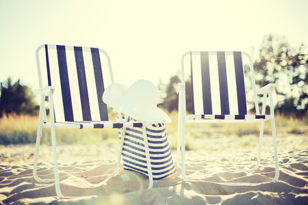 lounges: furniture and summer holidays concept - two beach lounges with beach bag and white hat on the beach Stock Photo