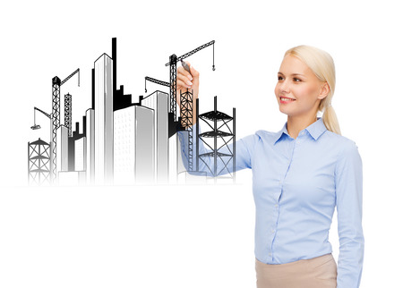 building, construction, architecture and industrial concept - businesswoman drawing construction site or industrial building with a marker photo