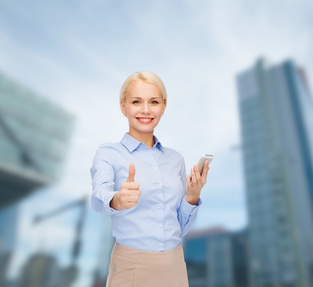 business, technology, internet and education concept - friendly young smiling businesswoman with smartphone showing thumbs up photo
