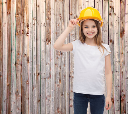 construction and people concept - smiling little girl in protective helmet photo