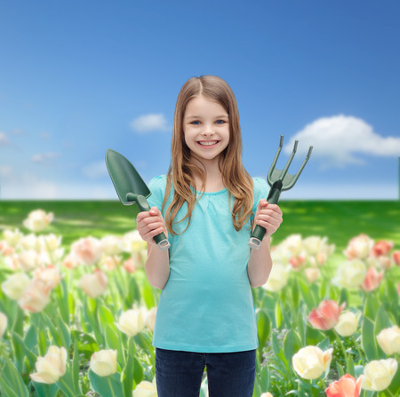 garden and people concept - smiling little girl with rake and scoop photo