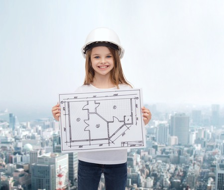 building, developing, construction and architecture concept - smiling little girl in white helmet showing blueprint Stock Photo