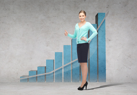 business, gesture and office concept - smiling businesswoman showing thumbs up with growing chart on the back photo