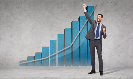 winning stock: business, office, growth or success concept - happy businessman with hands up celebrating victory in front of the concrete wall with graph