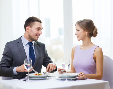 restaurant, couple and holiday concept - smiling couple eating appetizers at restaurant photo