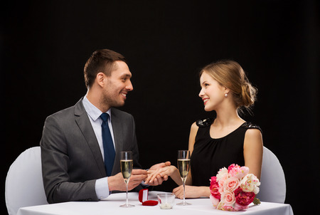 restaurant, couple and holiday concept - smiling man putting on finger engagement ring at restaurant photo