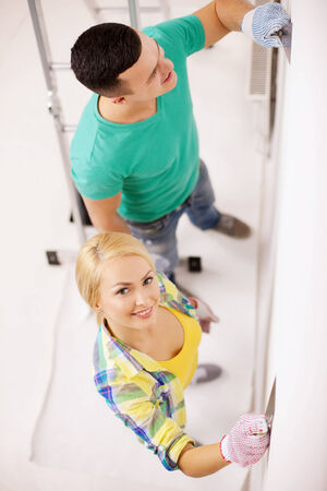 repair, renovation and home concept - smiling couple doing renovations at home photo