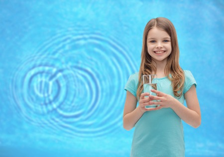 health and beauty concept - smiling little girl with glass of water Imagens
