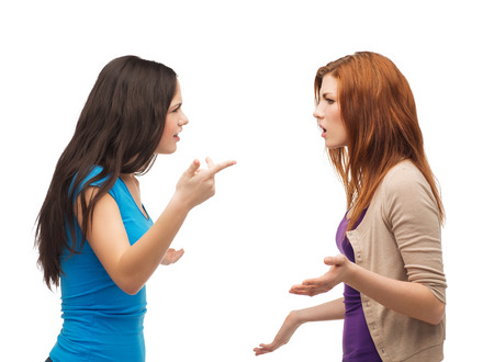 angry teenager: bullying, friendship and people concept - two teenagers having a fight