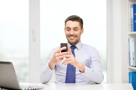 business, office and technology concept - smiling businessman with laptop computer and smartphone at office photo