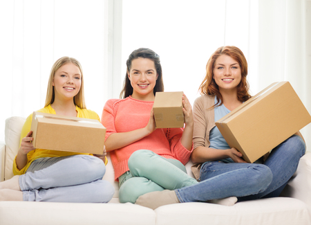 three gift boxes: transportation, post and friendship concept - three smiling teenage girls with cardboard boxes at home