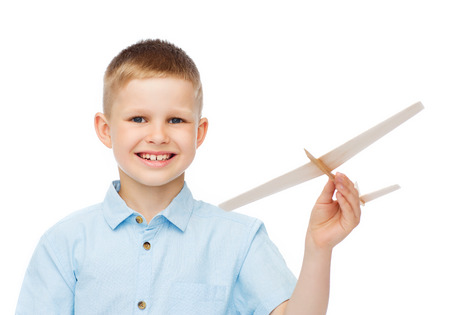dreams, future, hobby and childhood concept - smiling little boy holding a wooden airplane model in his hand photo
