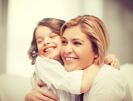 little girl smiling: bright picture of hugging mother and daughter Stock Photo