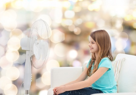 summer, weather and equipment concept - smiling little girl sitting on sofa with big fan at home photo