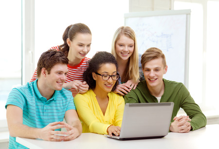 education, technology and college concept - five smiling students looking at laptop at school photo