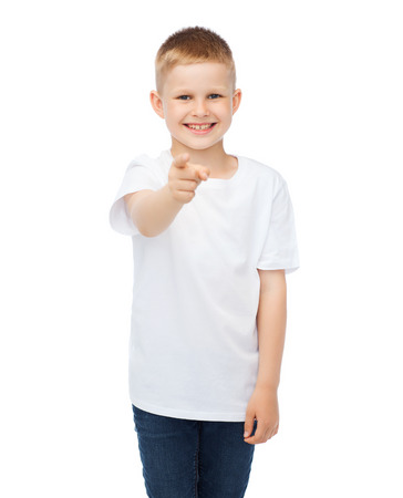 gestures, advertisement, childhood and happy people concept - happy little boy in blank white t-shirt pointing at you photo