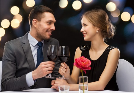 romantic dinner: restaurant, couple and holiday concept - smiling young couple with glasses of red wine looking at each other at restaurant