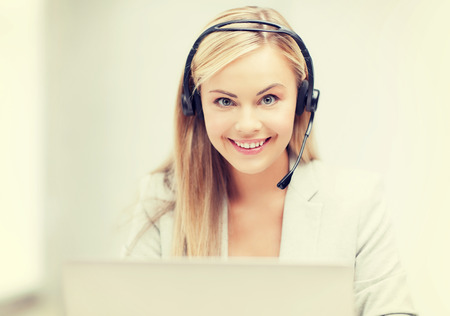 computer operator: smiling female helpline operator with headphones and laptop