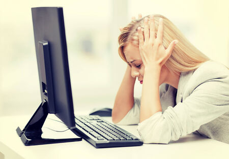 picture of stressed businesswoman with computer at work photo