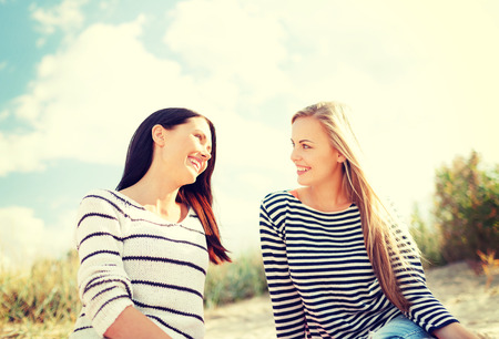 two friends talking: summer, holidays, vacation, happy people concept - smiling girlfriends having fun on the beach