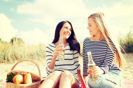 nonalcoholic beer: summer, holidays, vacation, happy people concept - smiling girlfriends with bottles of beer or non-alcoholic drinks on the beach