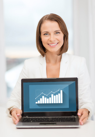 education, business, technology and internet concept - smiling woman with laptop computer in office photo