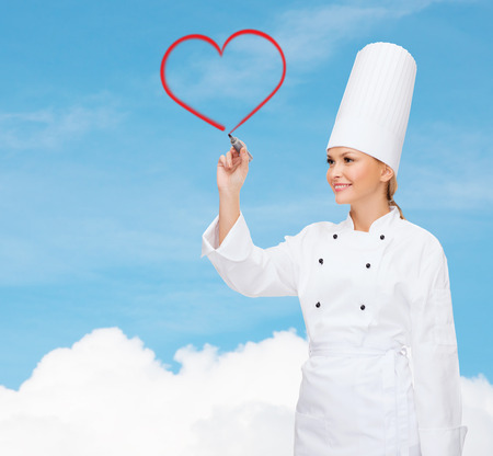 cooking, new technology , advertisement and food concept - smiling female chef with marker writing something on virtual screen photo