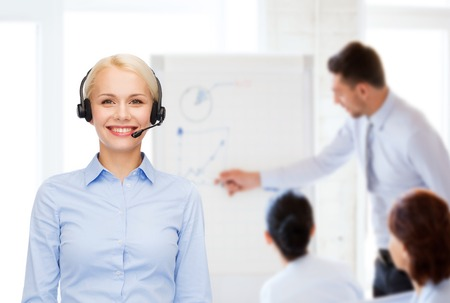 client meeting: business and office concept - friendly female helpline operator with headphones