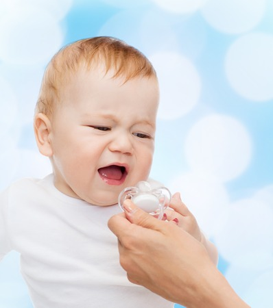 spoiled: child and toddle concept - crying baby with dummy