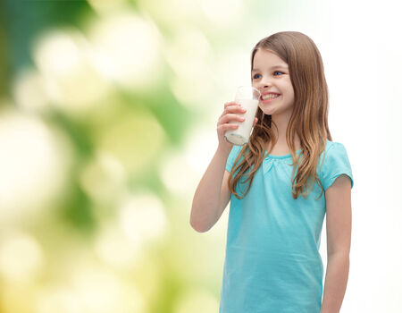 preteen  pure: health and beauty concept - smiling little girl drinking milk out of glass Stock Photo