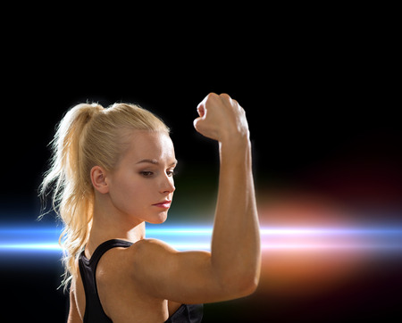 tough girl: fitness and diet concept - close up of beautiful athletic woman flexing her biceps Stock Photo
