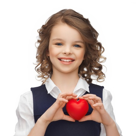 pre teen girls: happy children, charity and health concept - picture of beautiful girl with small red heart Stock Photo