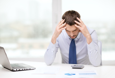 office, business, technology, finances and internet concept - stressed businessman with laptop computer and documents at office Stock Photo