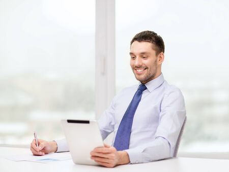 office, business, technology, finances and internet concept - smiling businessman with tablet pc computer and documents at office photo