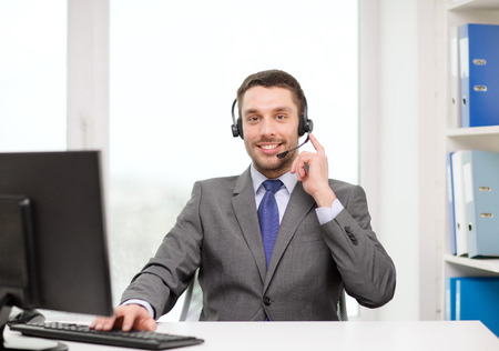 computer center: business, communication, technology and call center concept - friendly male helpline operator with headphones and computer at call center