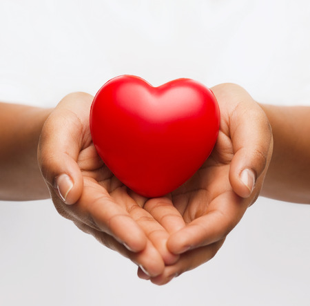 charitable: health, medicine and charity concept - close up of african american female hands with small red heart