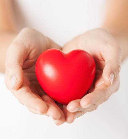 健康、医学および慈善の概念 - 小さな赤いハートを持つ女性の手のクローズ アップ