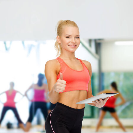 personal computer: sport, exercise, technology, internet and healthcare - smiling sporty woman with tablet pc computer showing thumbs up Stock Photo