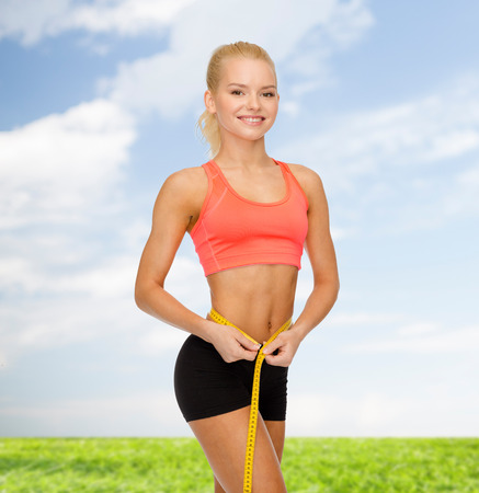woman measuring: diet, sport, fitness and heath concept - smiling beautiful sporty woman with measuring tape Stock Photo