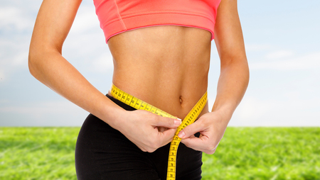 woman measuring: diet, sport, fitness and heath concept - close up of female hands measuring waist with measuring tape