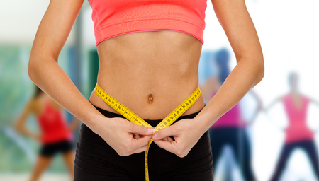 diet, sport, fitness and heath concept - close up of female hands measuring waist with measuring tape photo