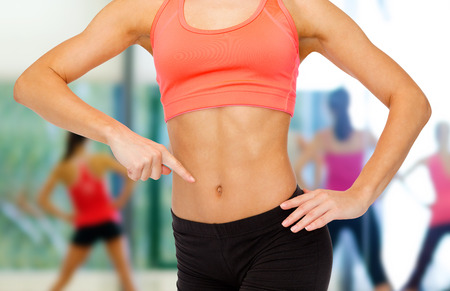 fitness, exercise and diet concept - close up of woman pointing finger at her six pack photo