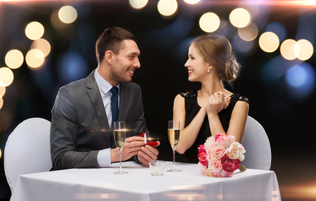 proposing: restaurant, couple and holiday concept - smiling man proposing to his girlfriend at restaurant Stock Photo