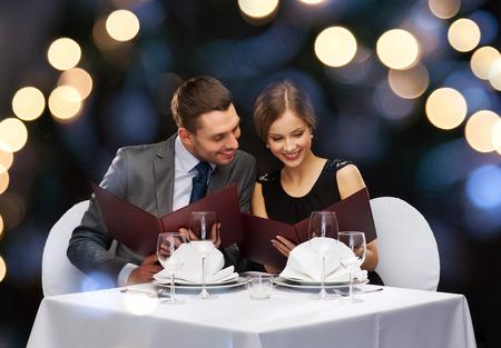 レストラン、カップル、休日のコンセプト - レストラン メニューとカップルの笑顔