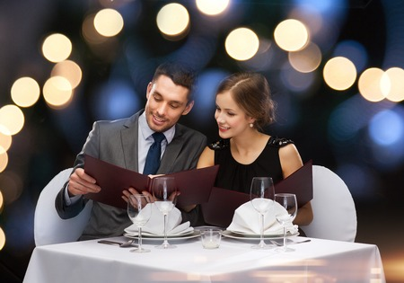 evening: restaurant, couple and holiday concept - smiling couple with menus at restaurant Stock Photo