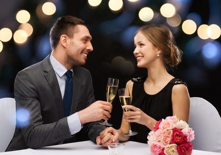 レストラン、カップル、休日のコンセプト - カップル レストランでお互いを見てシャンパン グラスに笑みを浮かべて