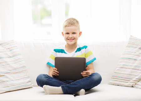 kids playing video games: home, leisure and new technology concept - smiling little boy with tablet pc computer at home